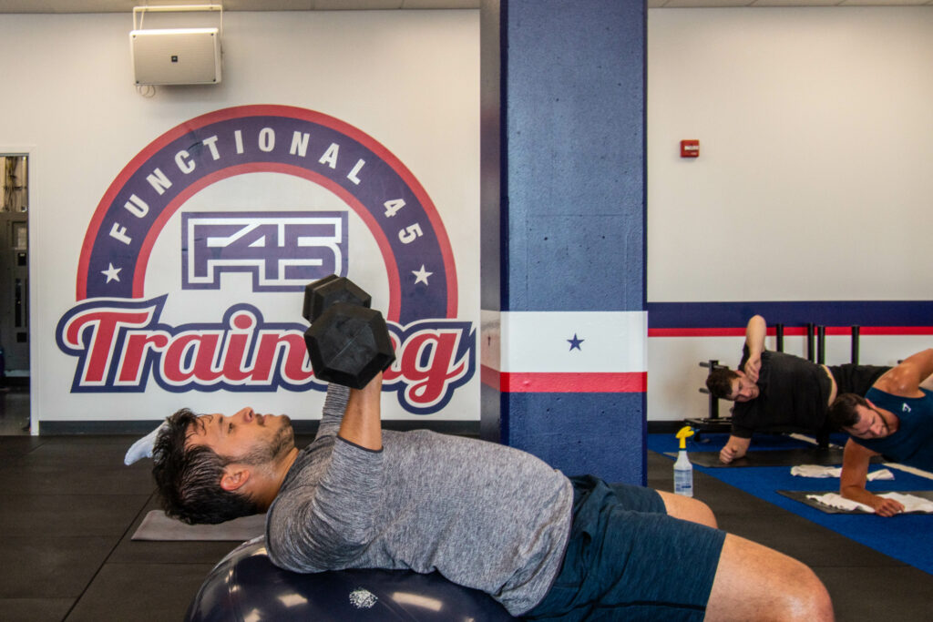 Man lifting in front of F45 sign