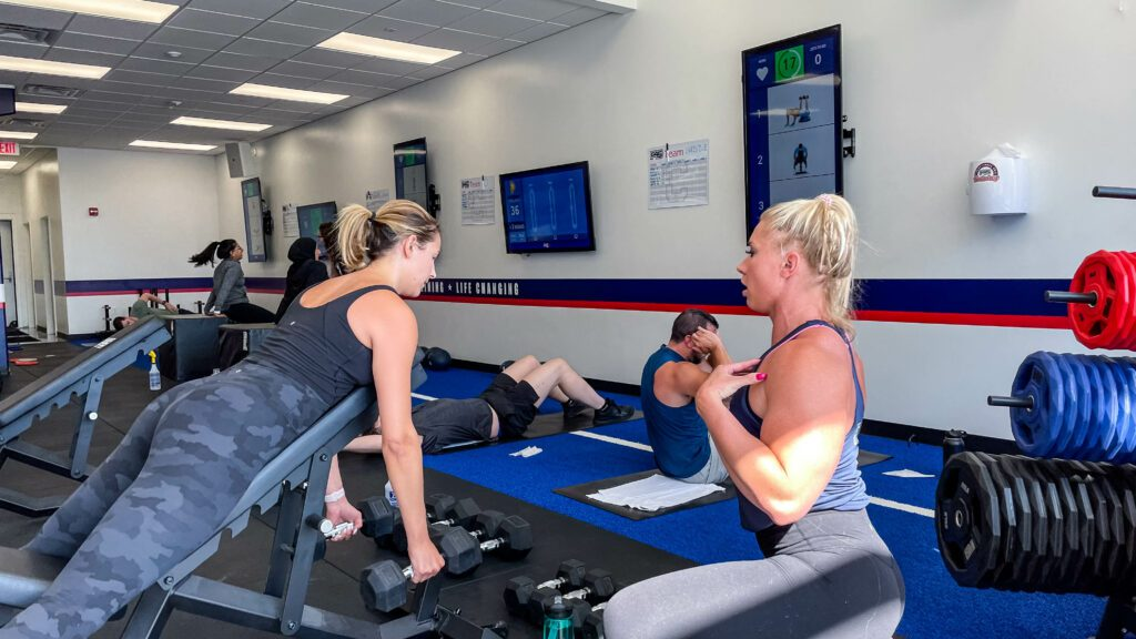 A F45 coach helping a person exercising